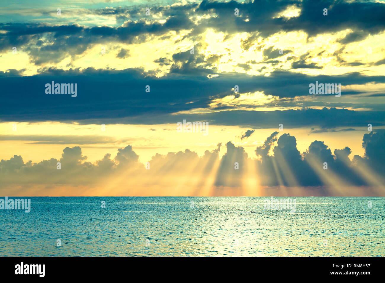 Hermoso paisaje del mar con un atardecer. Atardecer cielo con nubes y rayos de sol sobre el océano. Rayos de sol brillan romper a través de las nubes Foto de stock