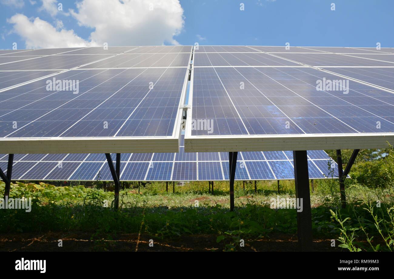 Paneles solares con bellas nubes cielo en el patio de la casa. Imagen De Stock