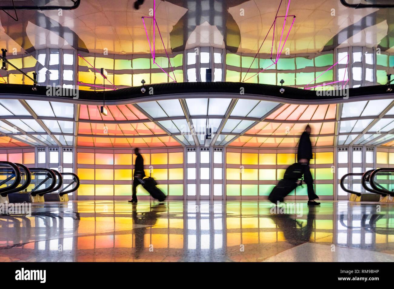 Los pasajeros de negocios, gente caminando, coloridas luces de neón instalación de arte por Michael Hayden, túneles peatonales, Chicago O'Hare Airport Terminal. Foto de stock