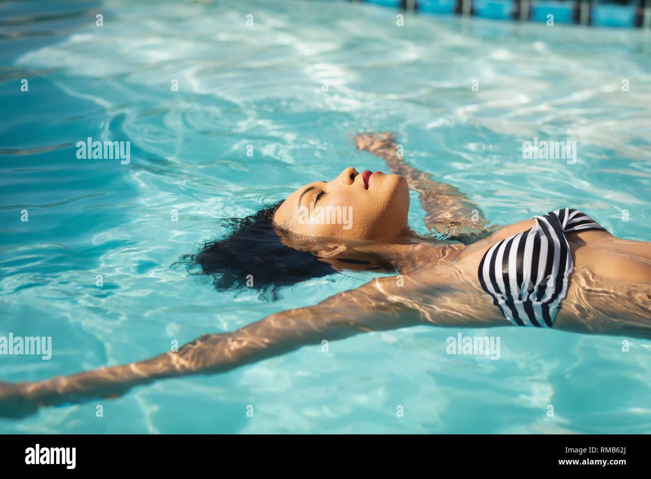 Joven mujer de raza mixta flotando en la piscina Foto de stock