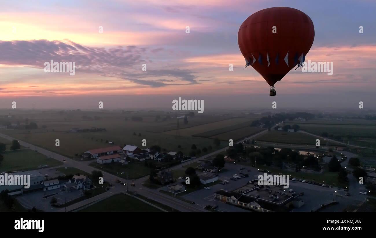 Vista aérea del amanecer con globos aerostáticos despegando con bujías visto por un zumbido Foto de stock