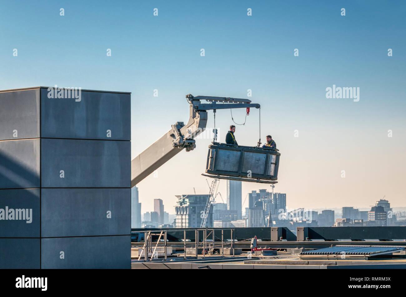 Dos trabajadores se preparan para descender desde la parte superior de un edificio alto trabajando desde un soporte de acceso. El horizonte de la ciudad de fondo. Imagen De Stock