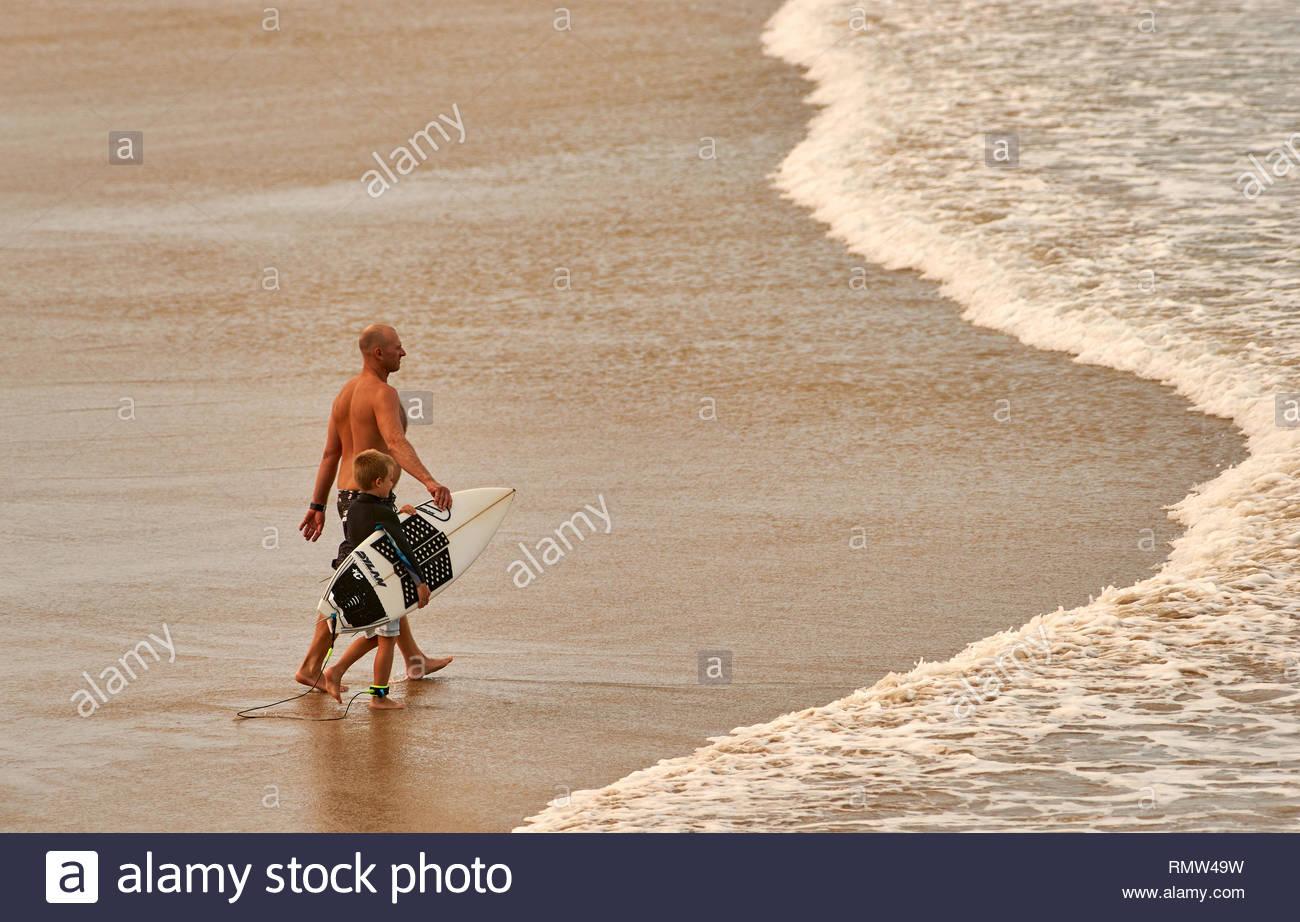 Un hombre lleva a su hijo en el océano, orientándolo como él aprende a manejar su tabla de surf por sí mismo; en Turners Beach, Yamba, NSW; durante el calor del verano. Imagen De Stock