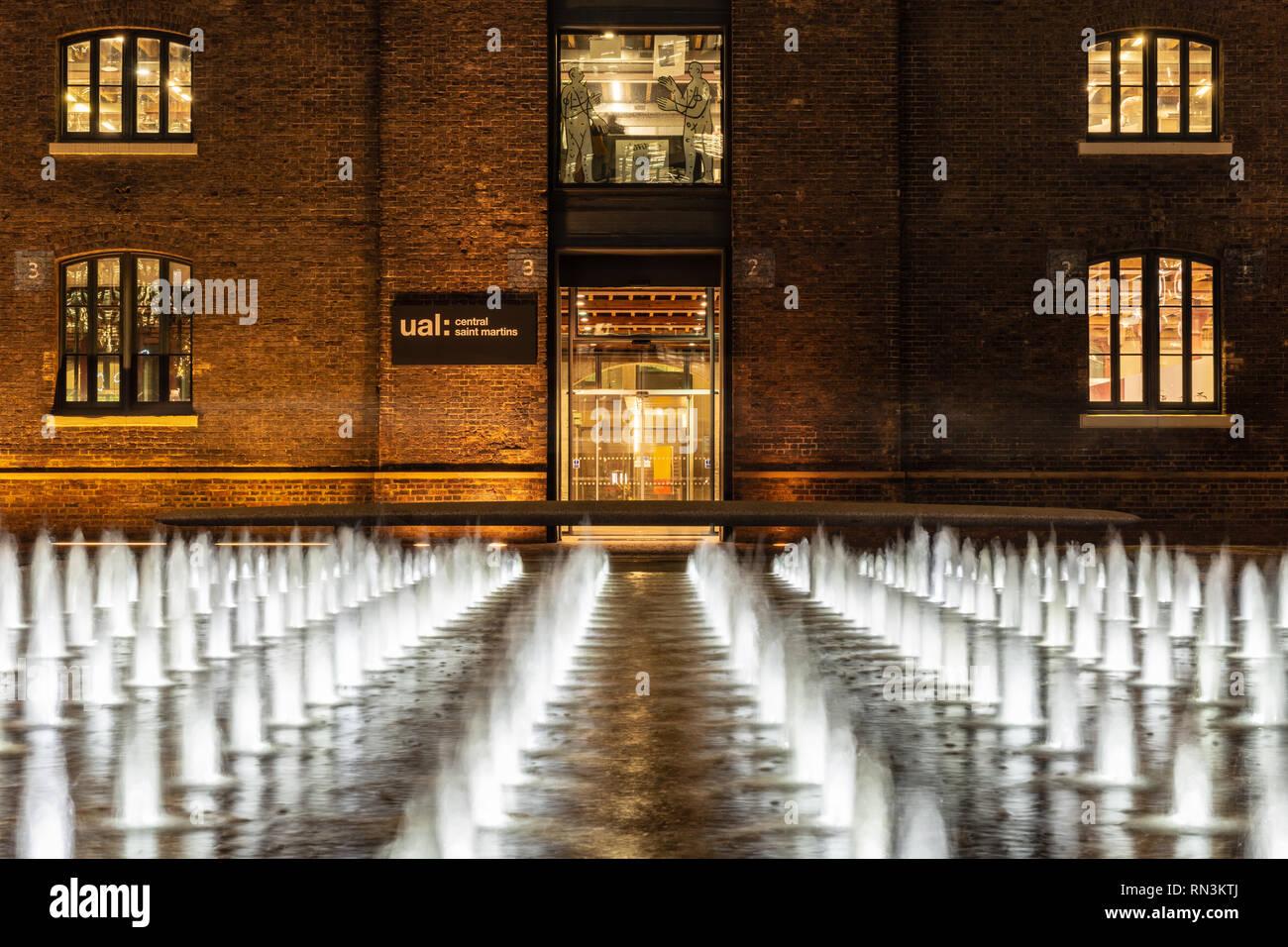Londres, Inglaterra, Reino Unido - 20 de diciembre de 2018: Las fuentes están iluminados por la noche en la plaza exterior Grannary Central Saint Martin's College de la Universidad de Foto de stock
