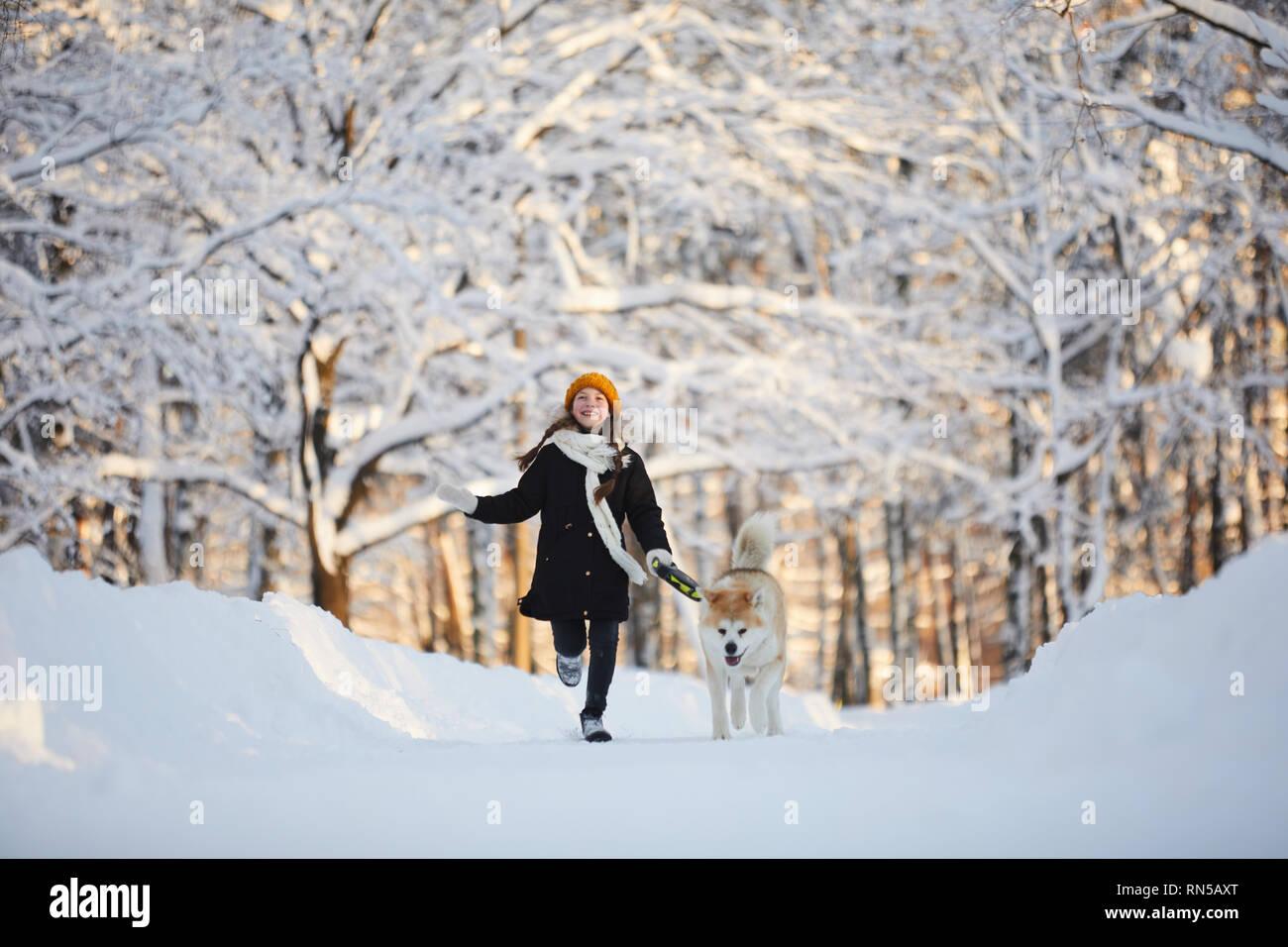 Chica caminar perro en Winter Park Foto de stock