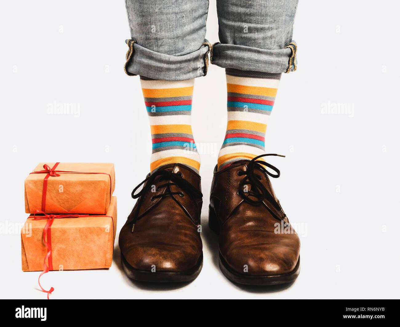 8d6ac9d0 Gerente de oficina en elegantes zapatos, pantalones azules brillantes,  coloridos calcetines y cajas con regalos sobre un fondo blanco, aislado.  Close-up.