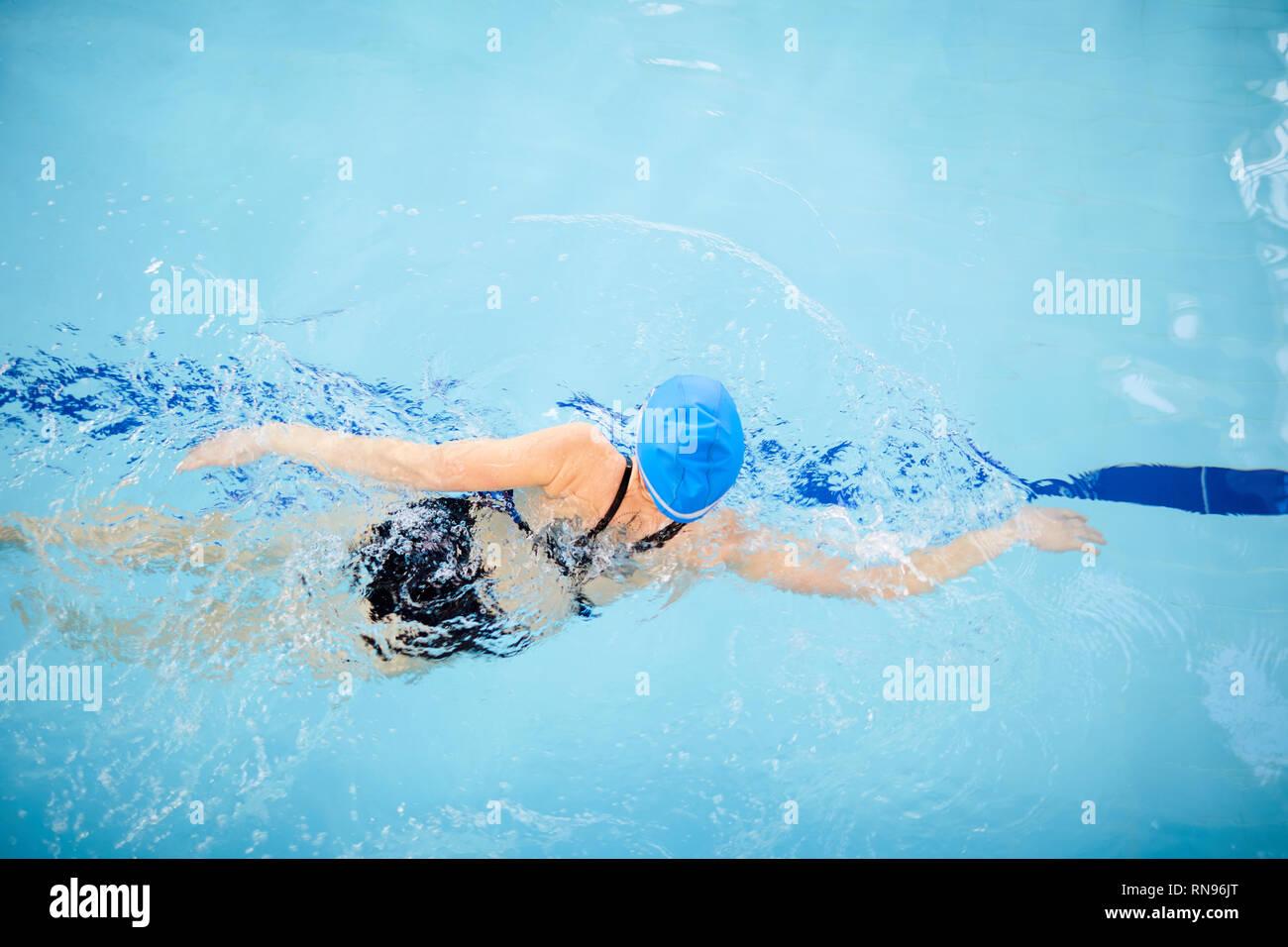 Mujer irreconocible nadar en piscina Foto de stock