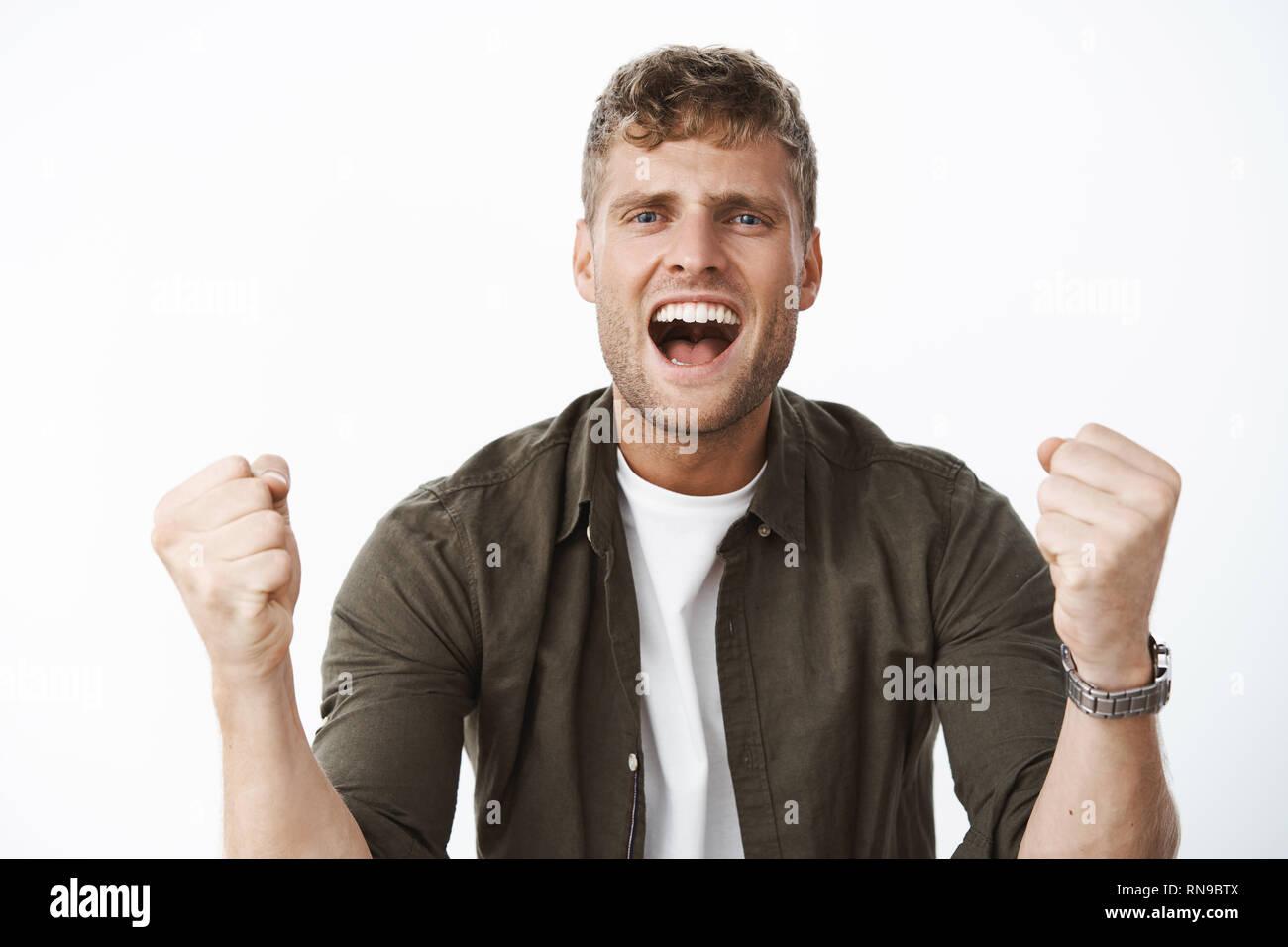 Guy aclamando con entusiasmo y alegría gritando en apoyo de cámara palabras del apretamiento puños en alegría y ser asertivo, estimular la confianza, fomentar Imagen De Stock