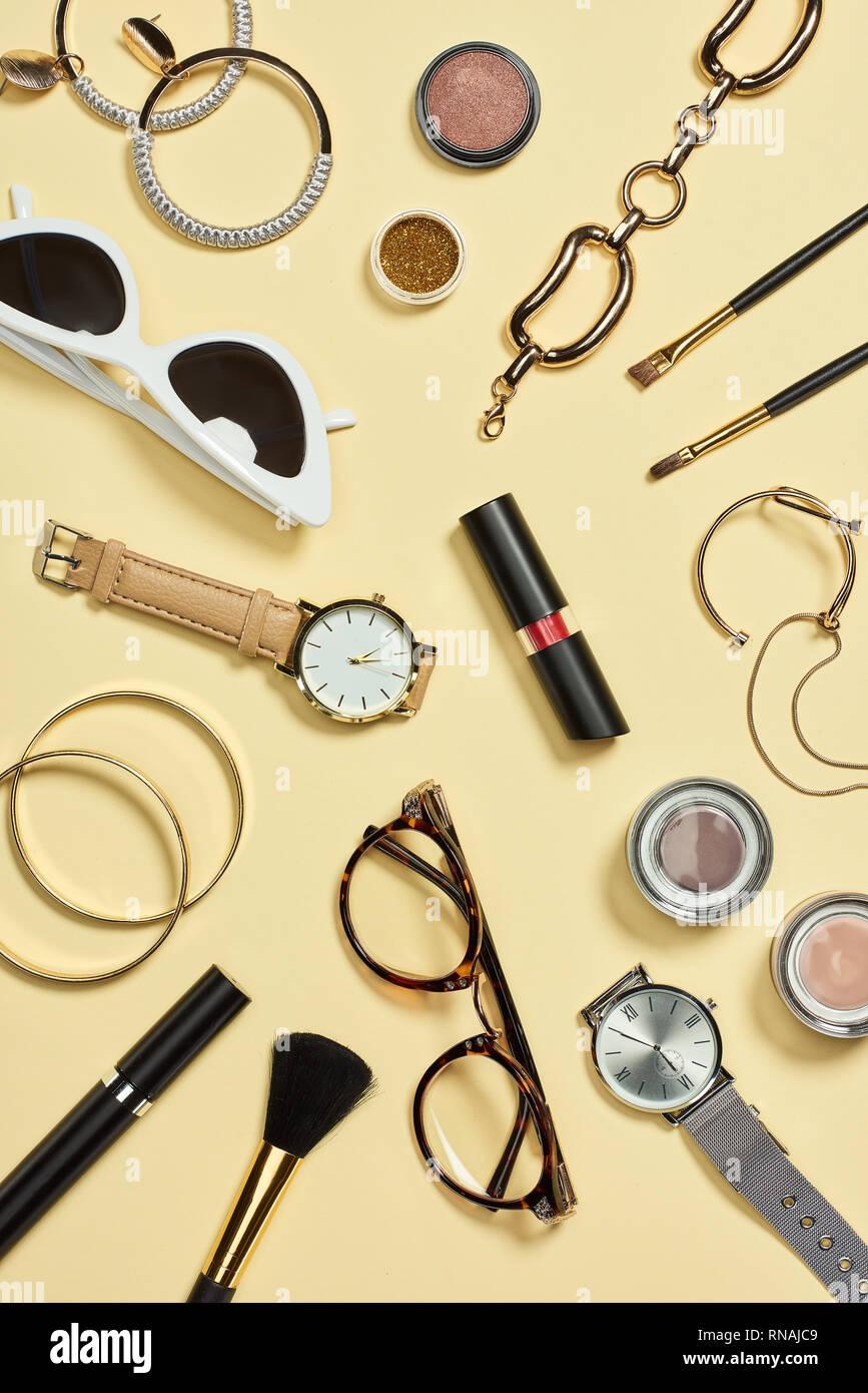 Vista superior de los relojes, lápiz labial, gafas, lentes de sol, sombreador de ojos, rubor, cepillos cosméticos, pulseras, aretes y rimel Foto de stock