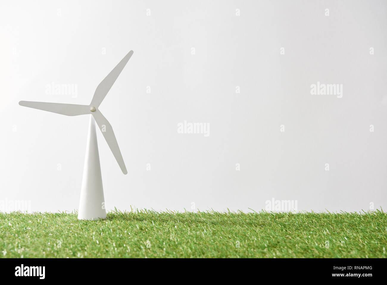 Modelo de molino de viento sobre la hierba verde y fondo blanco con espacio de copia Foto de stock