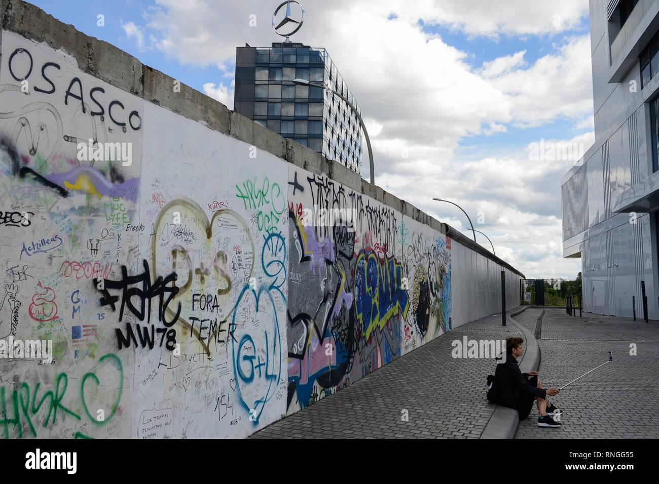 Alemania, Berlín, el muro, East Side Gallery, pared paintíngs y murales sobre la guerra fría y las paredes, graffitis en la parte trasera, detrás de la construcción con la estrella de Mercedes Benz, el símbolo del fabricante de automóviles alemán occidental Imagen De Stock