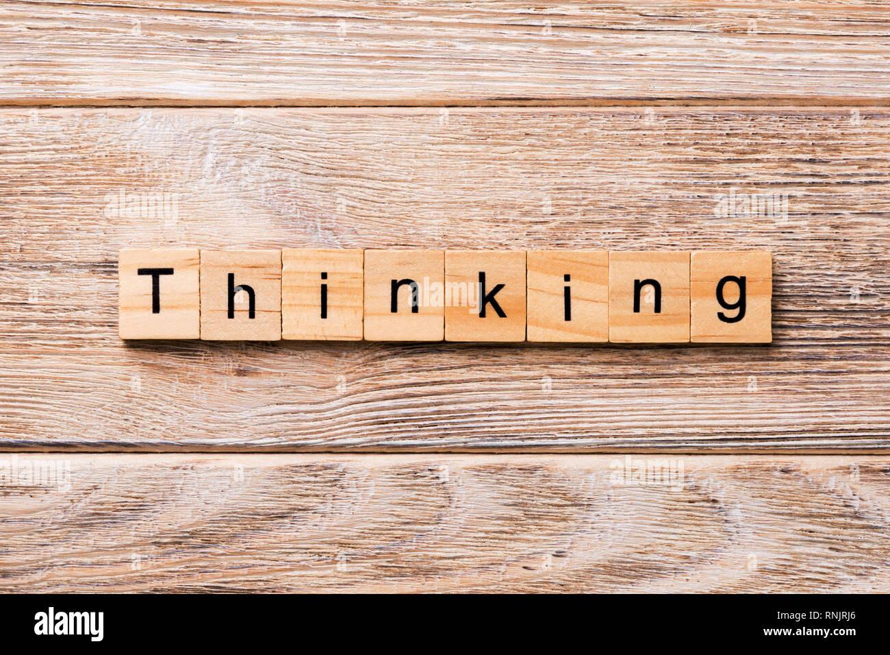 Pensando palabra escrita sobre un bloque de madera. Pensando en texto en tabla de madera para su diseño, concepto. Foto de stock