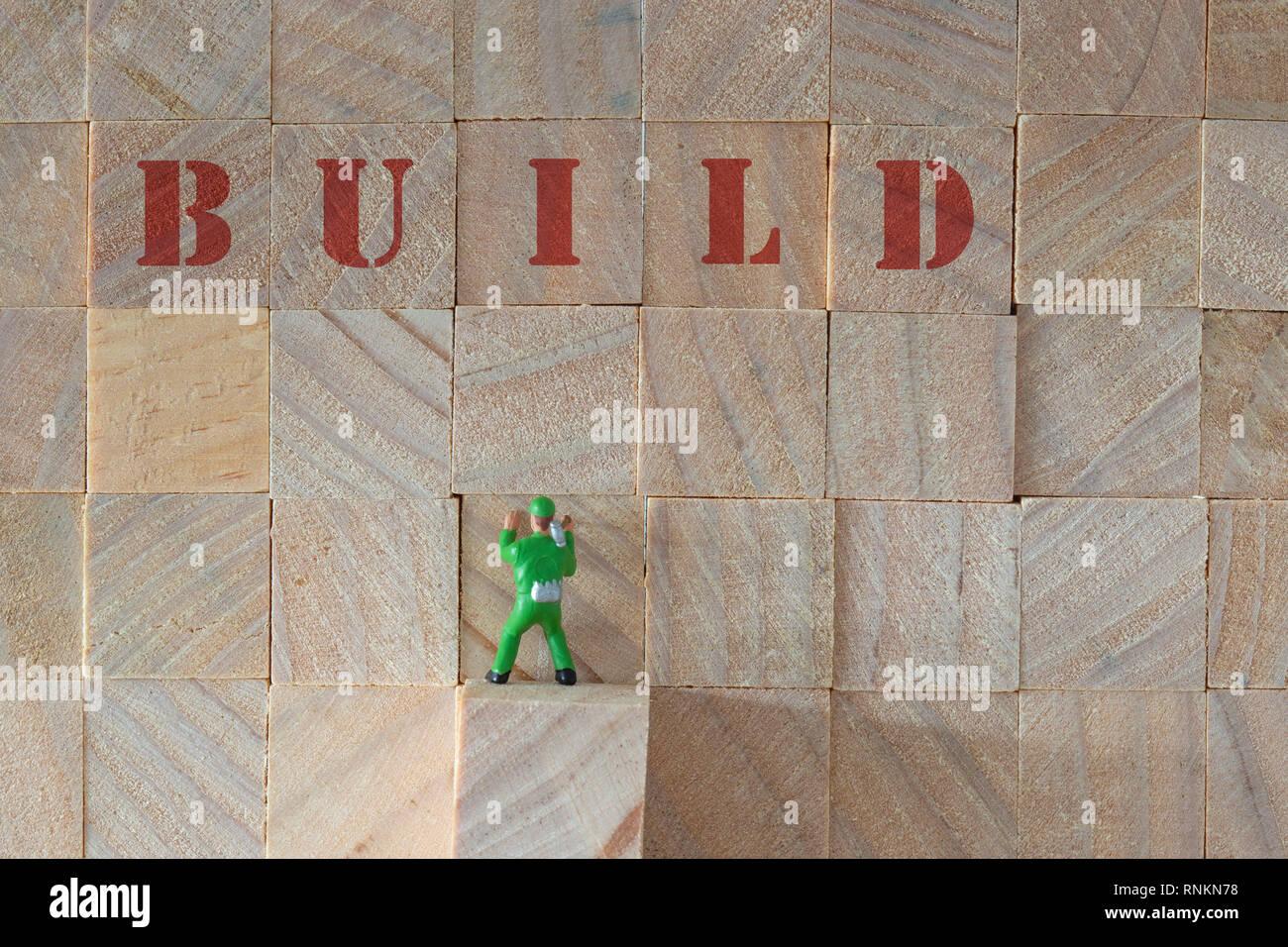 Apilado de madera con la palabra y construir un modelo a escala en miniatura Builder con un martillo. Foto de stock