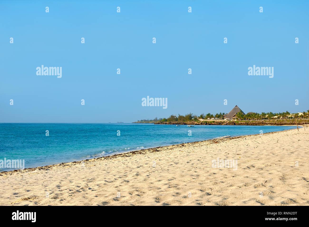 Vista de la costa con playa en Kenia, África. La gente, los vacacionistas y mar con olas y surf resort, edificios y bajo un cielo azul sin nubes. Imagen De Stock