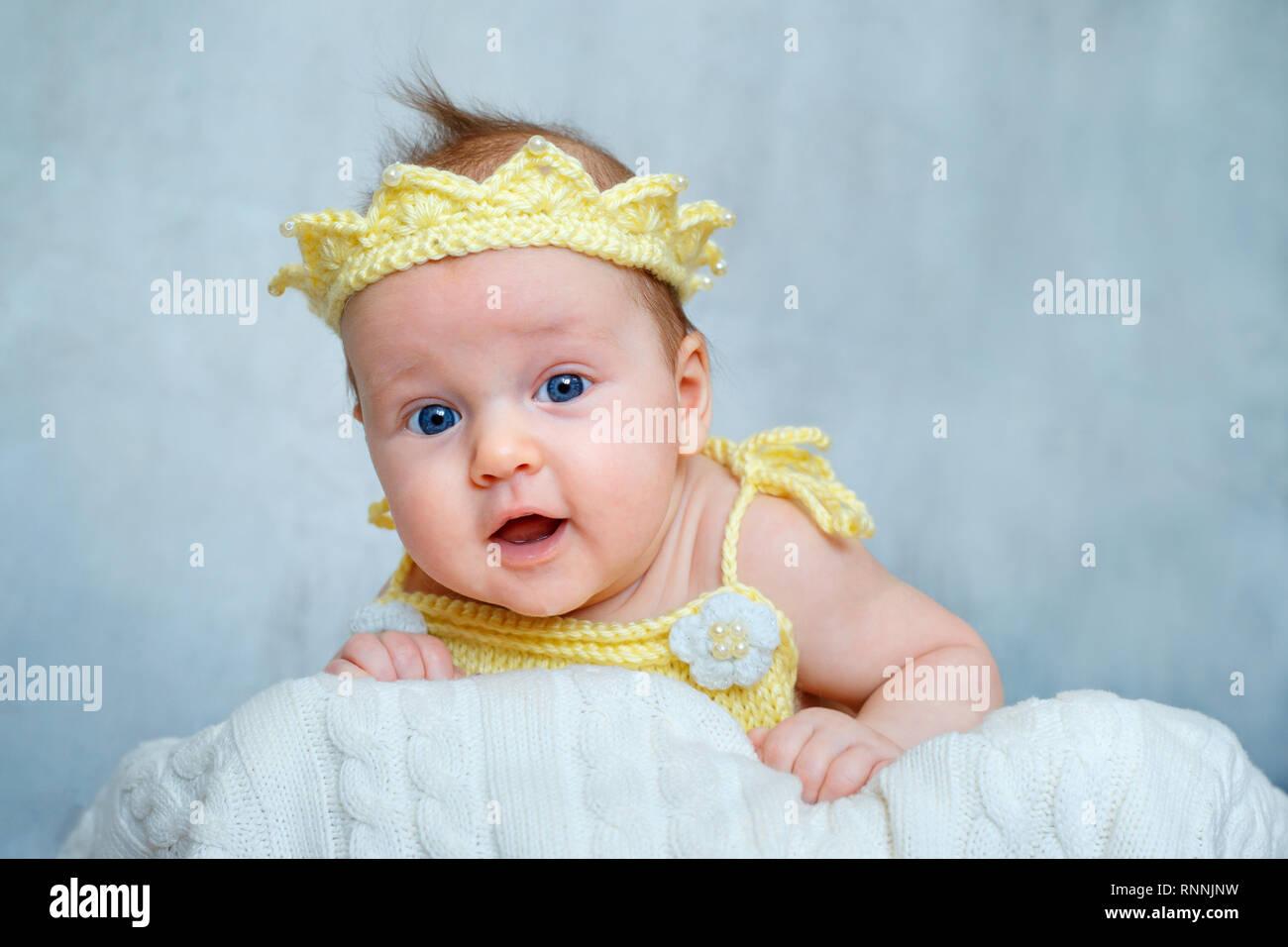 Retrato de un lindo bebé niña en amarillo corona tejida tumbado sobre su  estómago Imagen De 4661701e2e4