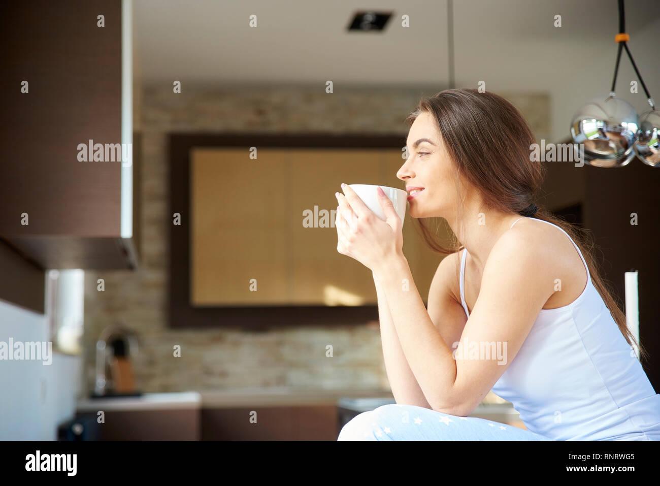 acdf67f3d5 Retrato de joven mujer vistiendo pijamas y beber su té de la mañana  mientras se relaja