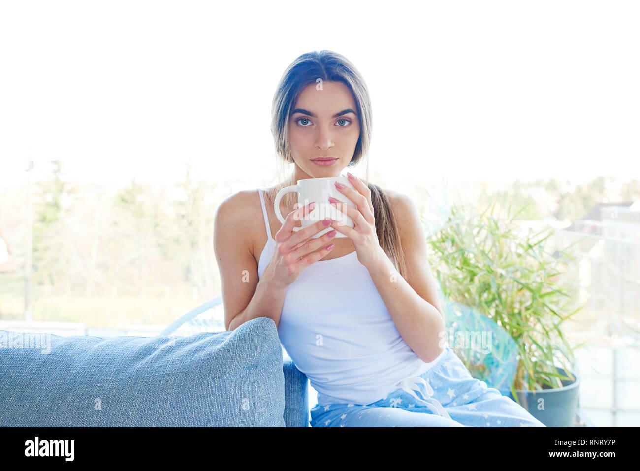 6e621db7e7 Retrato de joven mujer vistiendo pijamas y sosteniendo la taza en la mano  mientras se relaja