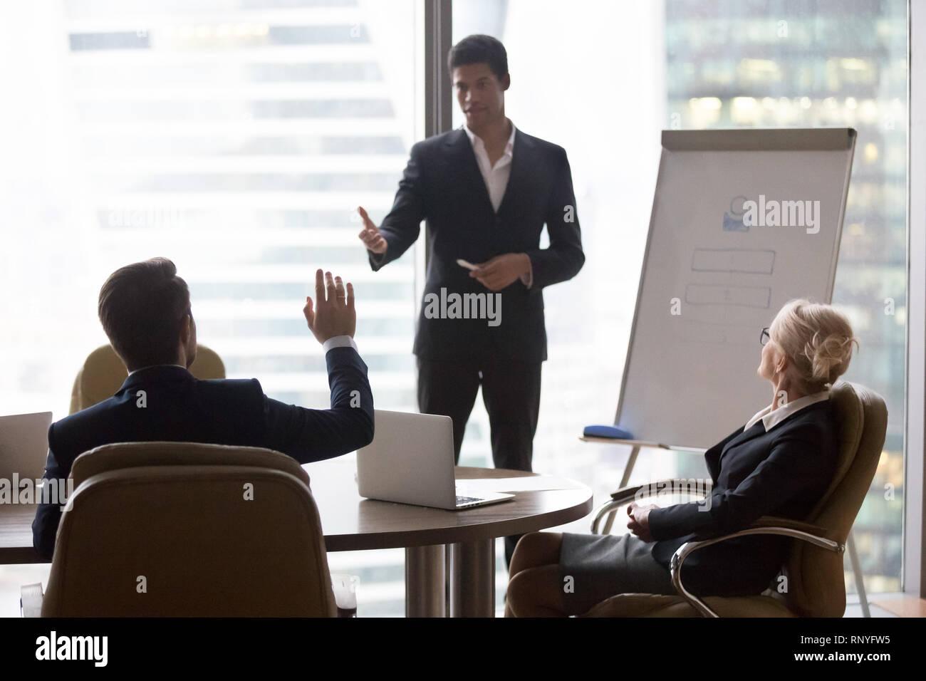 Empresario levantando la mano en la formación corporativa preguntas entrenador africano Foto de stock
