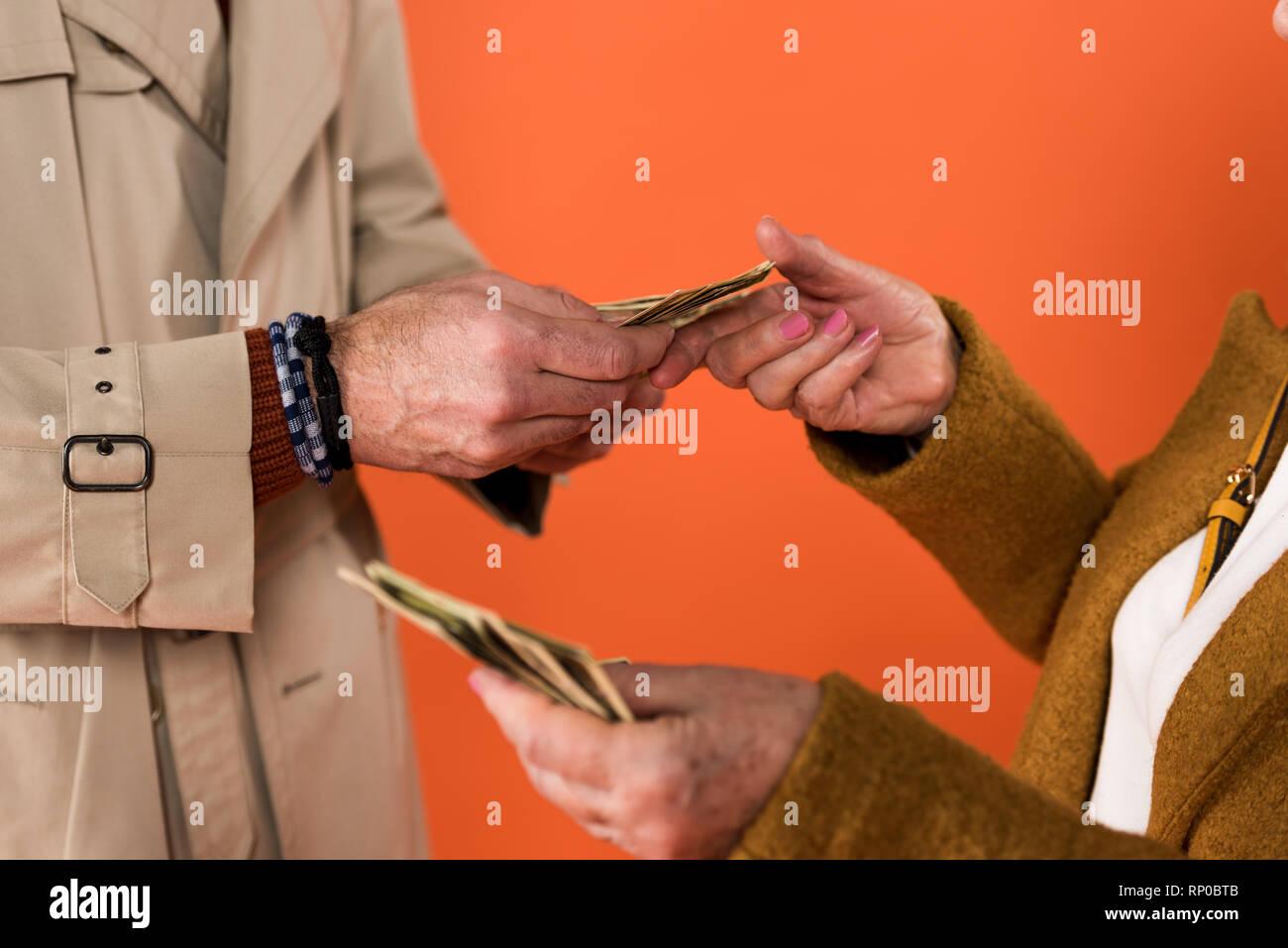 Vista recortada de alto par la celebración de billetes de dólar en manos aisladas sobre naranja Foto de stock