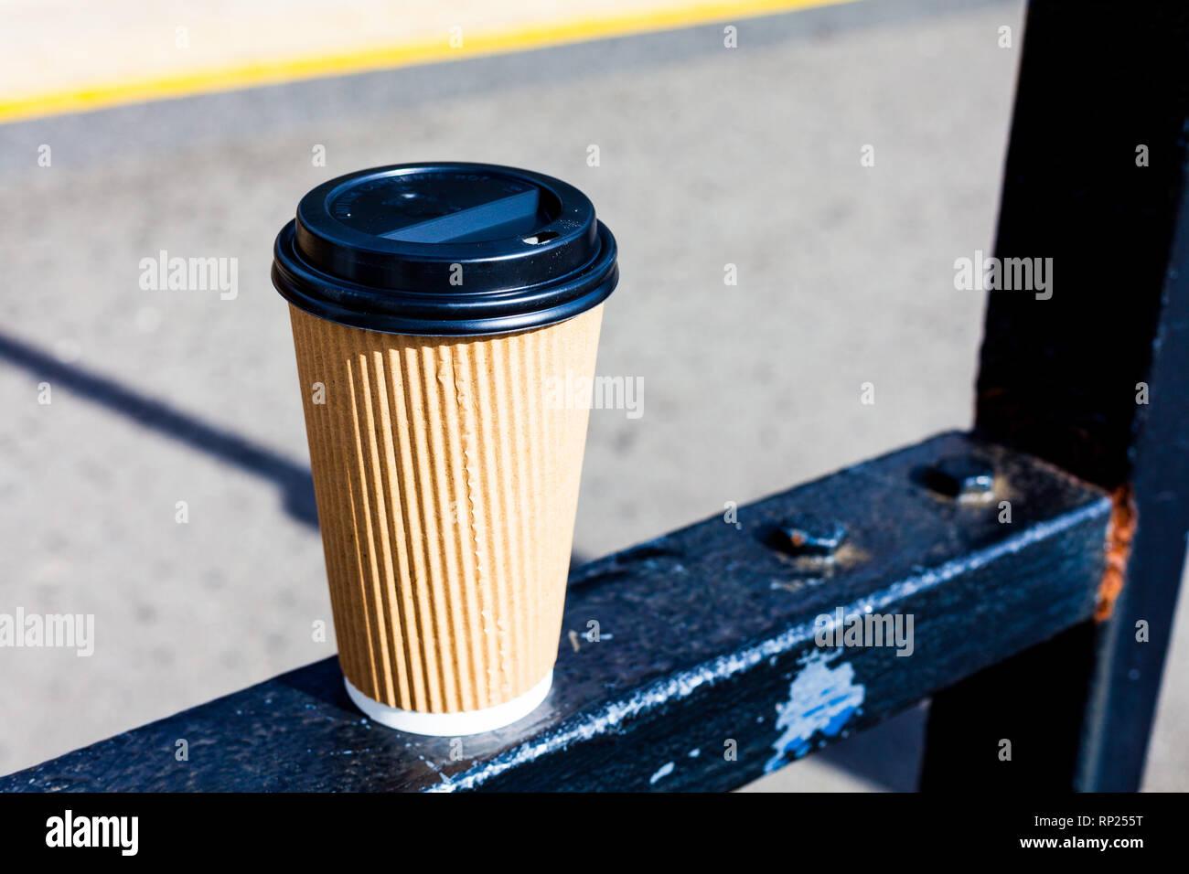 Café Espresso para llevar parado en la puerta de metal. Día soleado con café espresso en la cubeta de plástico Foto de stock