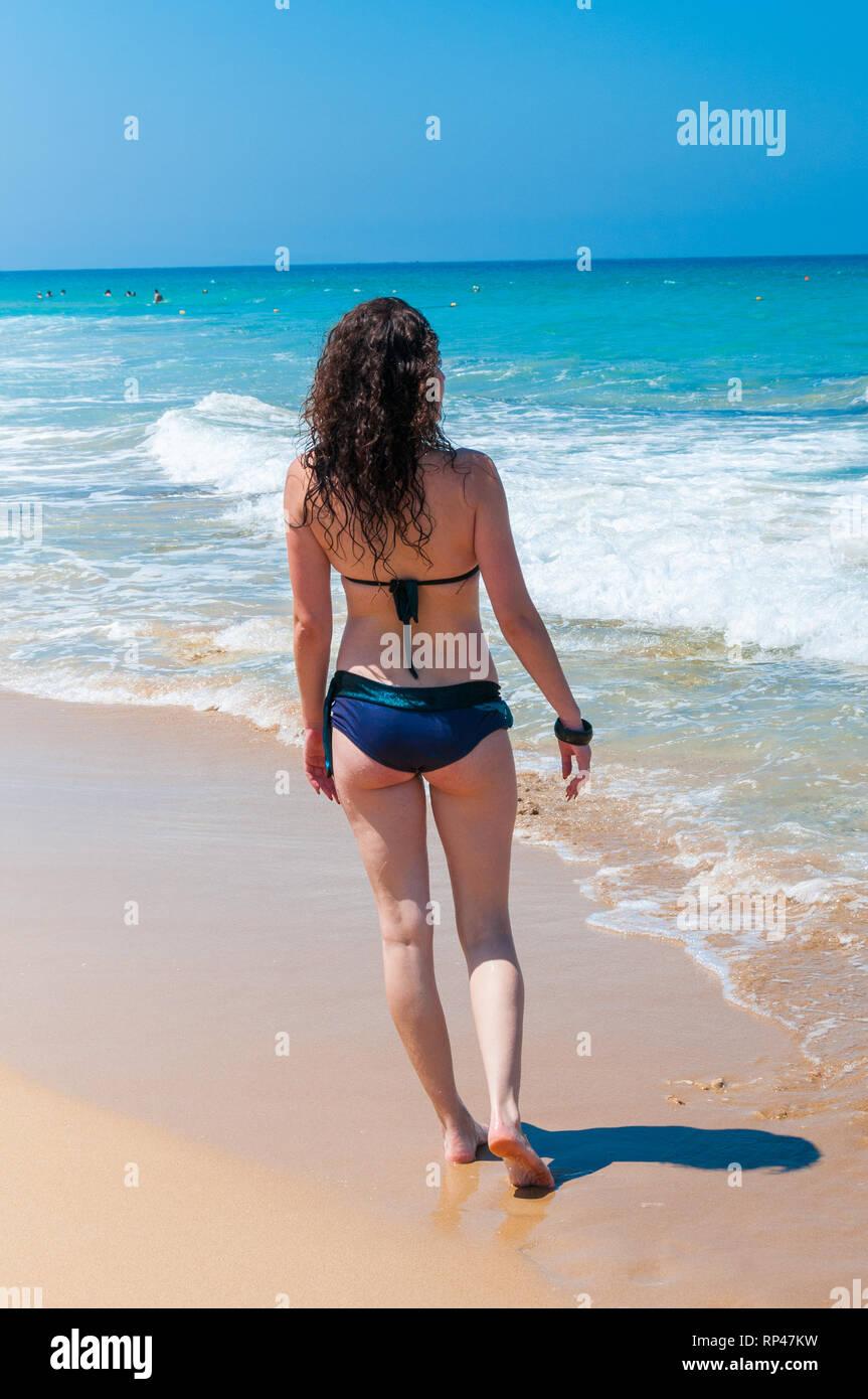 d0f0919f5b4c La chica del bikini azul paseos a lo largo de la costa salvaje hacia ...