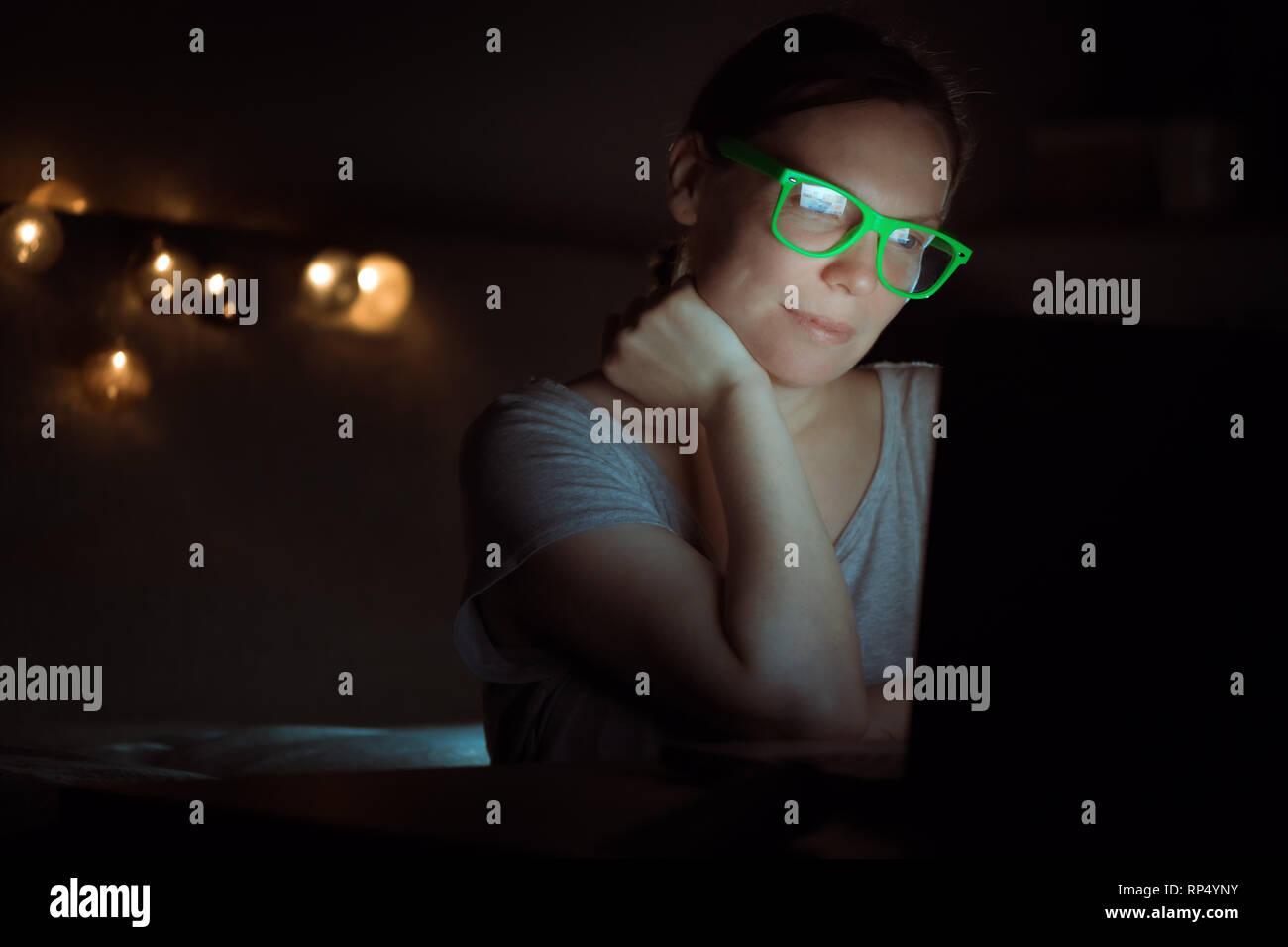 Mujer trabajando horas extraordinarias en un portátil a altas horas de la noche, low key retrato de mujer emprendedora en entornos de oficina doméstica Terminar tarea empresarial Foto de stock