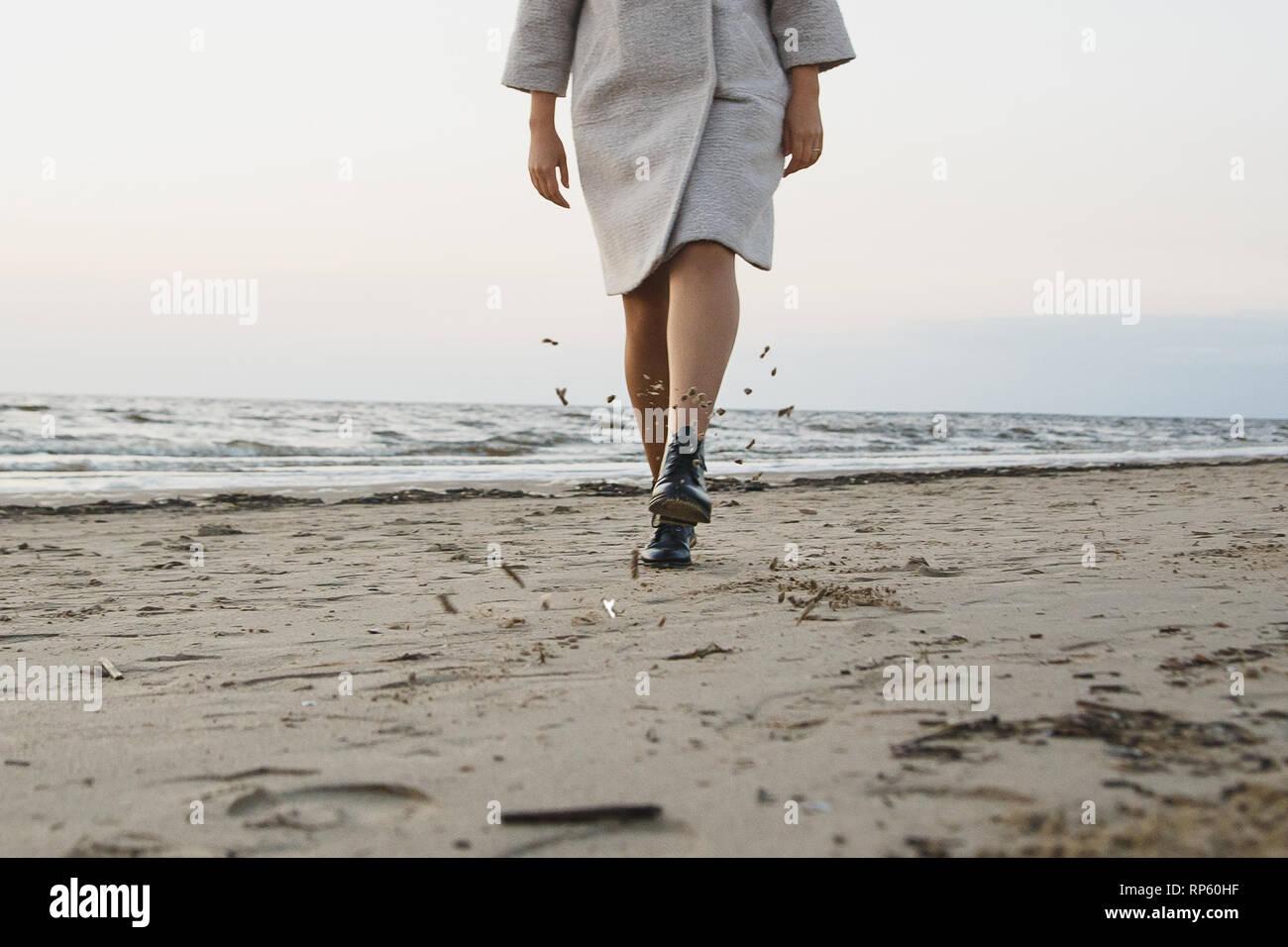 Mujer despreocupada en botas de cuero negro patada en la playa de arena. Volando arena mojada. Concepto El calzado de protección, resistencia al agua y al polvo. Foto de stock