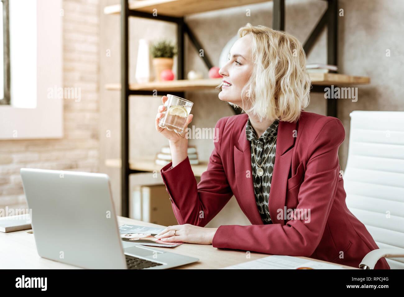 Curioso atractiva señora con amplia sonrisa calmar la sed con agua Imagen De Stock