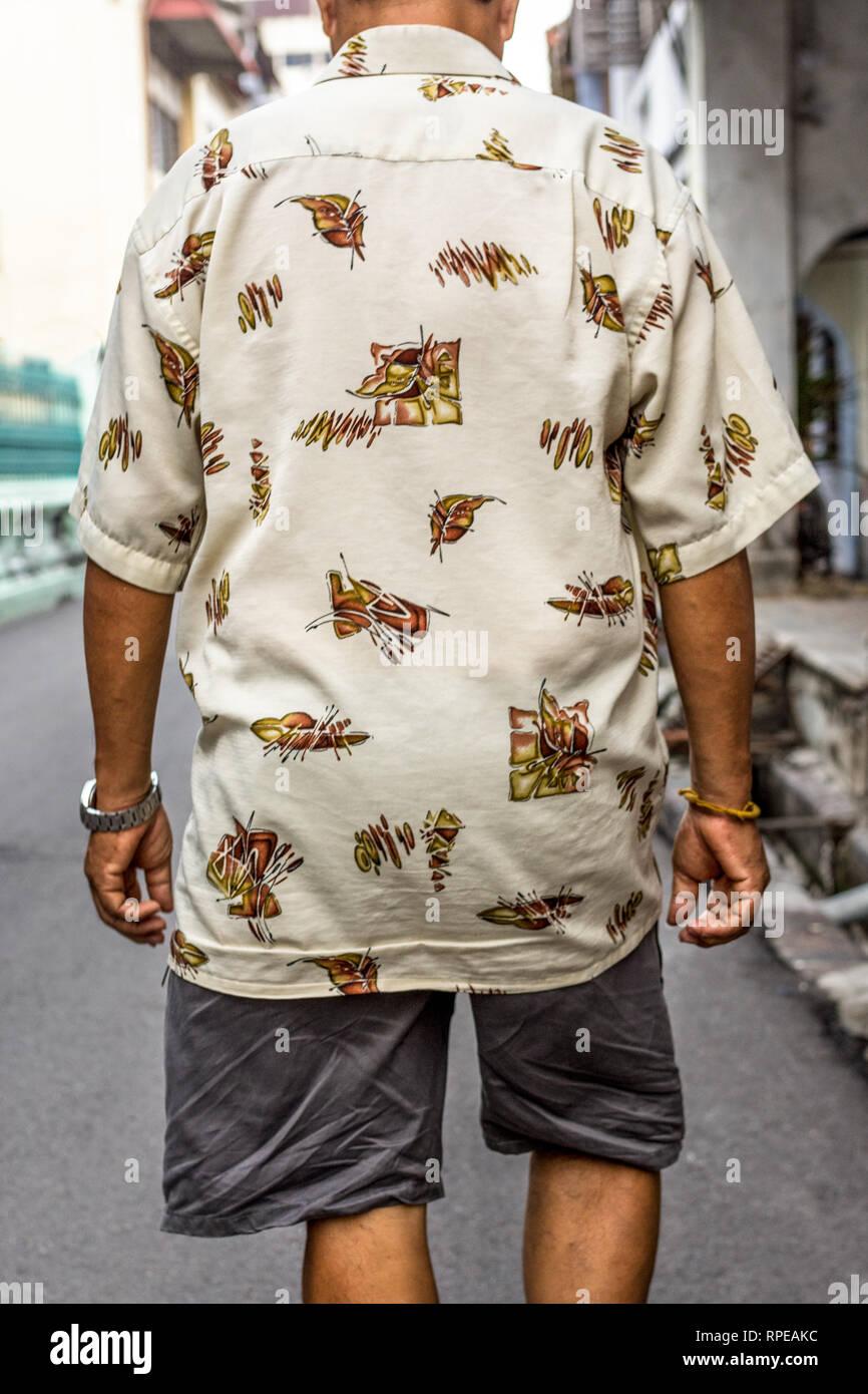 Un anciano en pantalones cortos y camisetas de manga corta se aleja de la cámara. Imagen De Stock