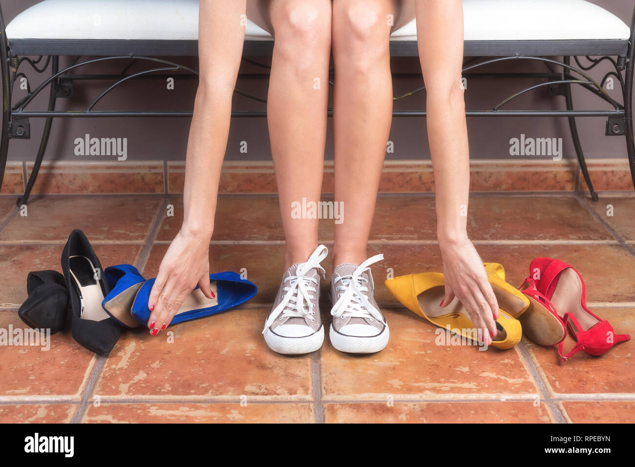 Mujer con perfecto piernas delgadas, elegir cómodas zapatillas más que incómodos zapatos con tacón de aguja . Imagen De Stock