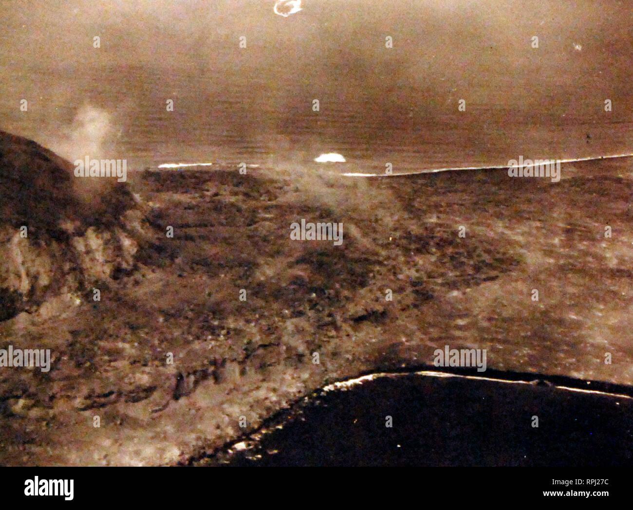 La batalla de Iwo Jima, en febrero y marzo de 1945. Mt. Suribachi en Iwo Jima. Daños causados por fuego naval y los bombardeos aéreos puede ser visto a lo largo de bluff y en la playa. Fotografiado por avión desde el USS Makin Island (CVE) 93 el día D, 19 de febrero de 1945. Foto de stock