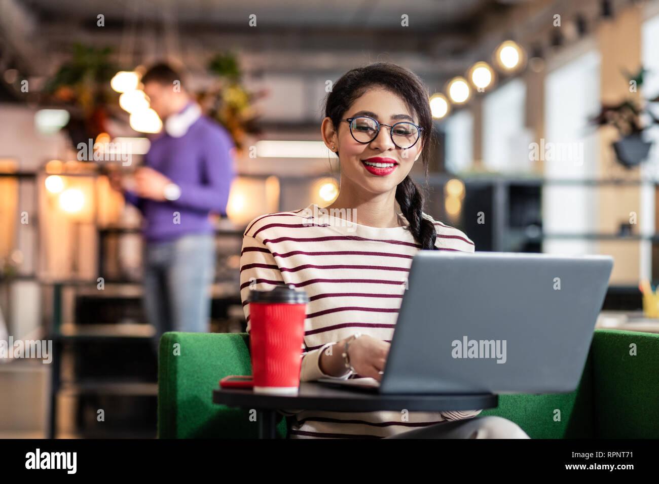 Niña morena encantadora trabajando en su portátil Foto de stock