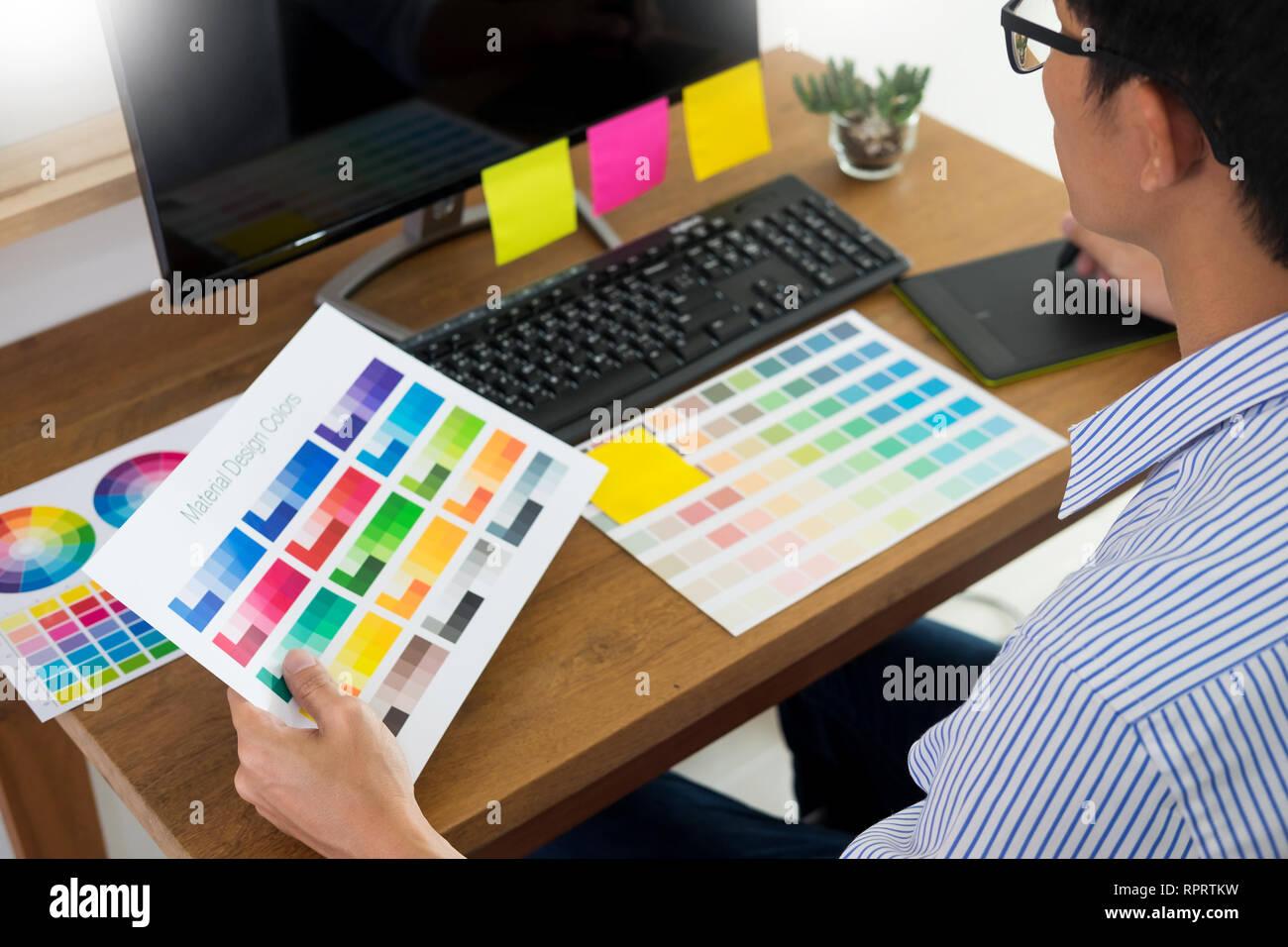 Editor de diseñador en el trabajo dibujar bocetos de un nuevo proyecto sobre la tableta gráfica y la paleta de colores sentado en una mesa con el equipo en el estudio o la oficina. Foto de stock