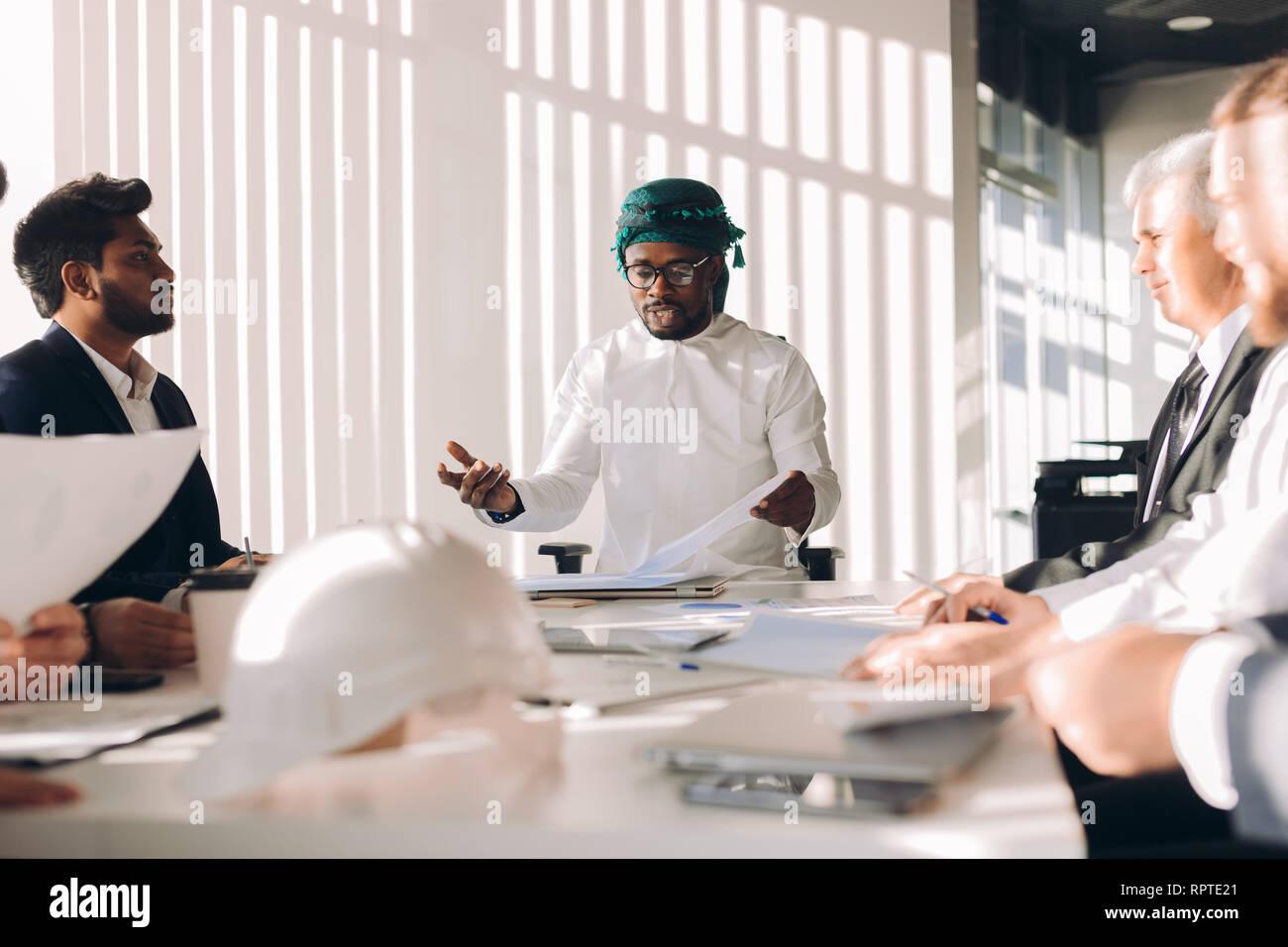 Arabian inversionista en blanco y gutra candura nacionales en la cabeza discutiendo la estrategia financiera de la empresa con su multirucial los gerentes hombres durante una reunión Foto de stock
