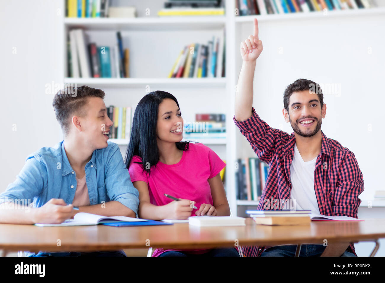 Laughing estudiante varón levantando la mano en el aula de la escuela Imagen De Stock