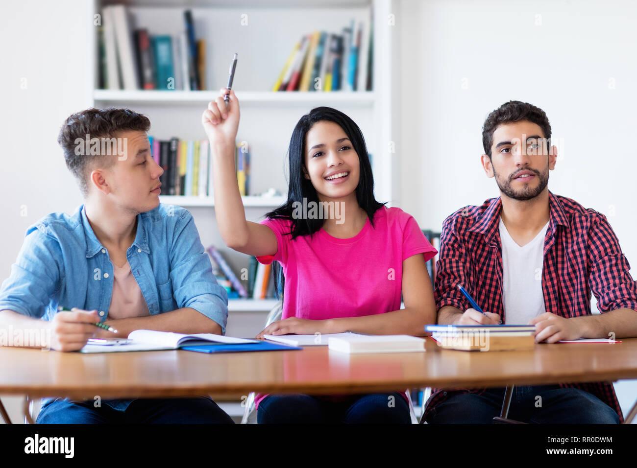 Laughing estudiante levantando la mano en el aula de la escuela Imagen De Stock