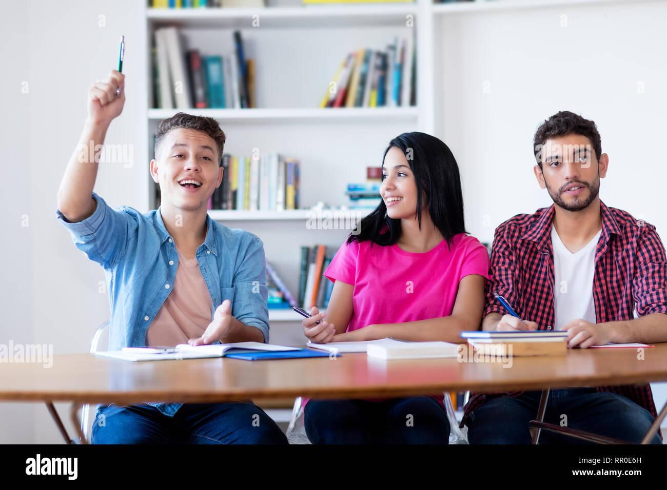 Estudiante varón caucásico levantando la mano en el aula de la escuela Imagen De Stock