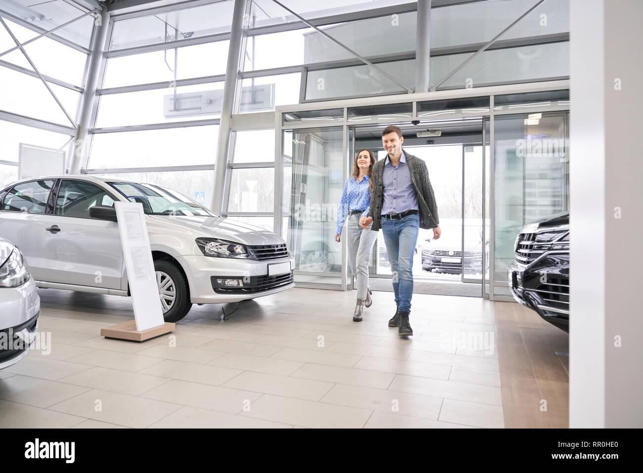 Hermosa pareja caminando en concesionario showroom, tomados de las manos y se van. Encantadora y hermosa mujer hombre sonriendo, posando y observando los automóviles en alquiler centro. Imagen De Stock