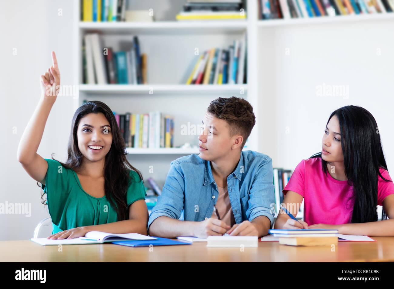 América estudiante levantando la mano en el aula de la escuela Imagen De Stock