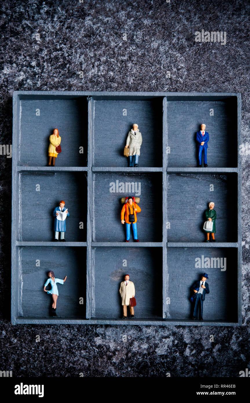 Figuras en miniatura en una caja con compartimentos, concepto para encasillar la gente Imagen De Stock