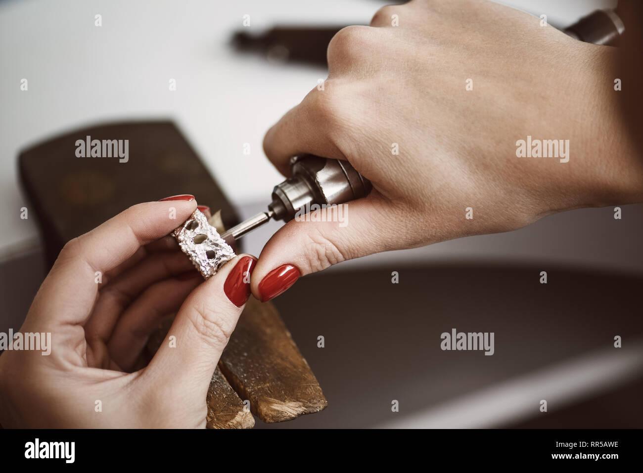 62c6dc12c2eb Manos de mujeres jeweler pulir un anillo de plata con máquina de molienda