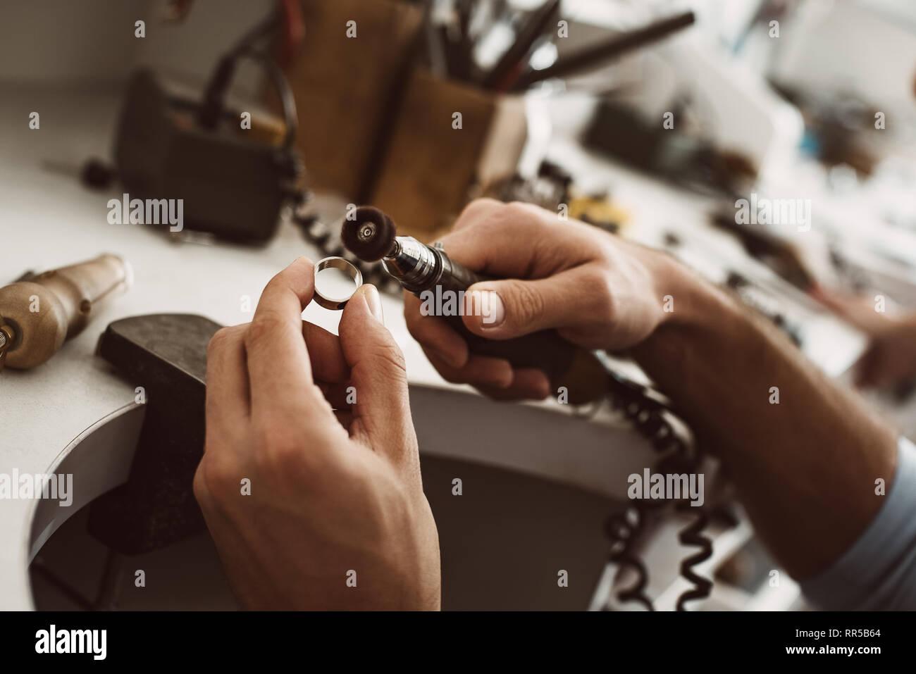 5832aa5f9635 En el camino hacia la perfección. Close-up de manos del joyero masculino  anillo