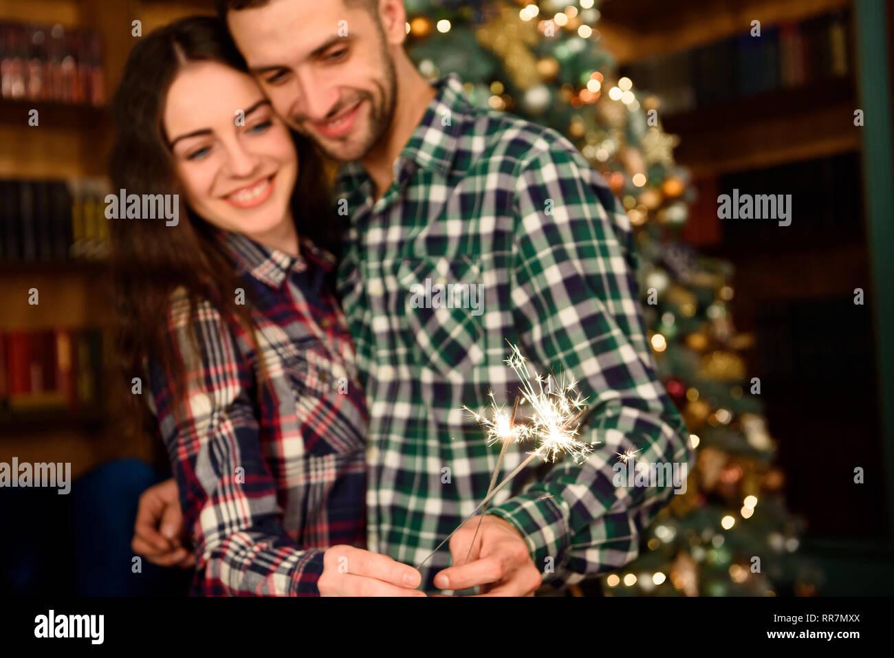 Estrellitas y un beso para Navidad. Kisser hermosa joven y la quema de estrellitas. Pareja amorosa en habitación de decoración de Navidad. Imagen De Stock
