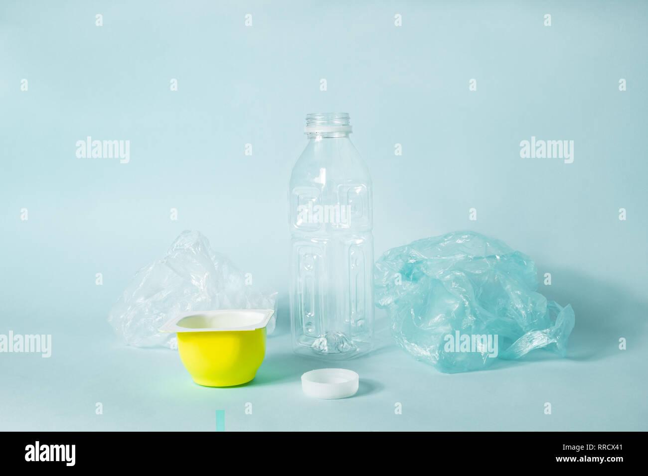 """Artículos de plástico desechables de uso diario sobre fondo azul. El concepto de """"huella ecológica"""" de humano: el tapón del vaso de plástico y envases de alimentos que don Imagen De Stock"""