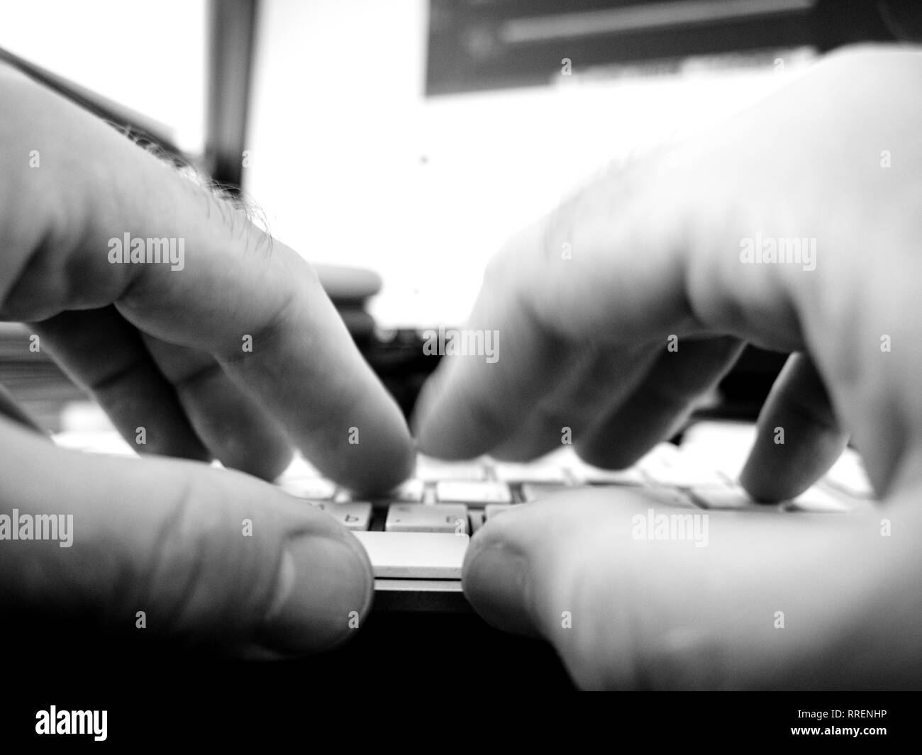 Manos masculinas una escritura rápida trabajando en teclado de ordenador escrito reproduciendo con equipo moderno con tapas blancas y cirílico y caracteres ingleses - blanco y negro Foto de stock
