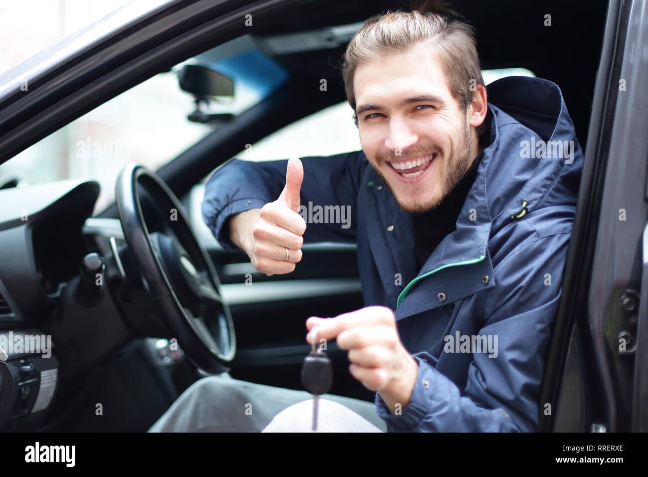 Hombre feliz mostrando el pulgar hacia arriba y las llaves de su coche Imagen De Stock
