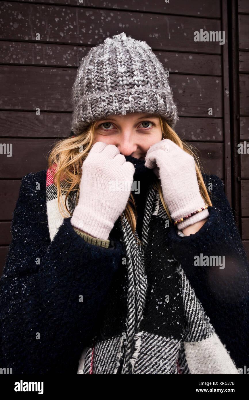Joven rubia con un gorro de punto de invierno que cubre parcialmente el rostro del frío Foto de stock