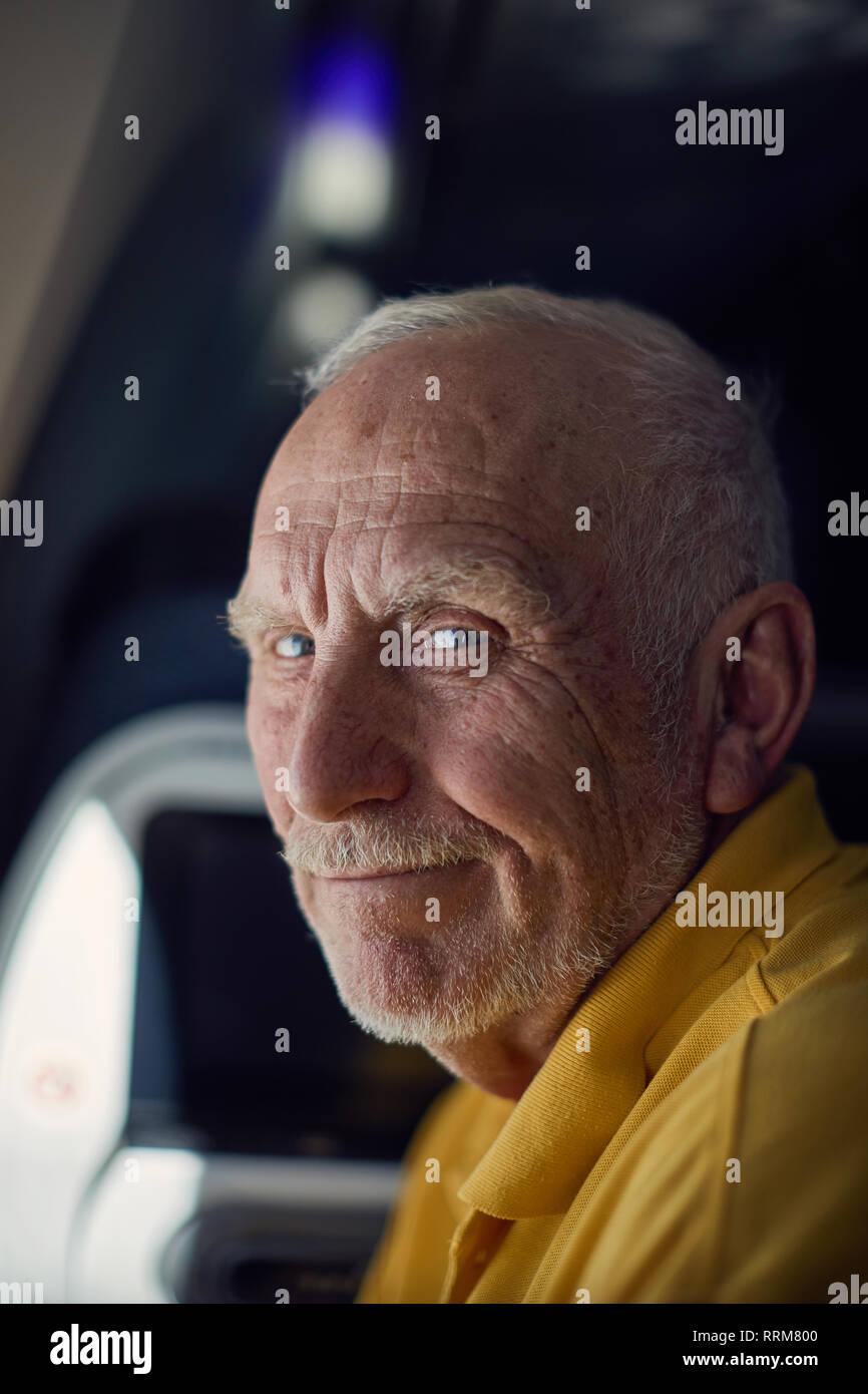 Amistoso masculino senior sonriendo mientras viaja en avión Imagen De Stock