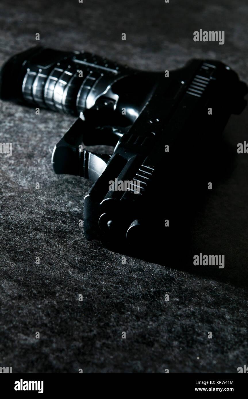 Pistola de negro en una luz espectacular - imagen de thriller portada del libro. Imagen De Stock