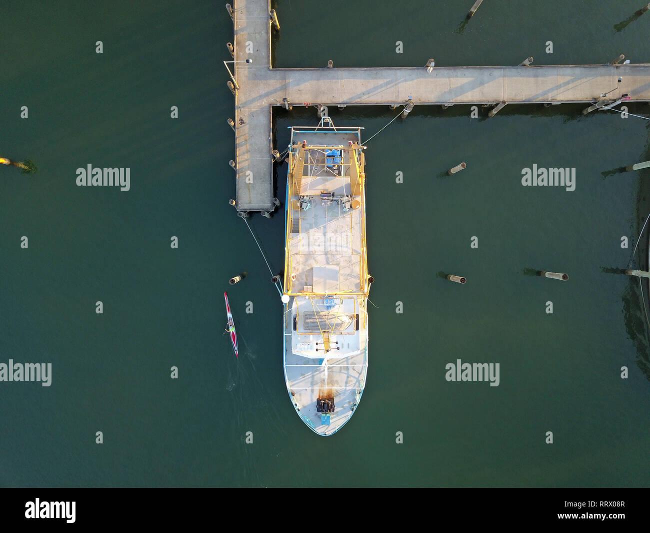Barco de pesca desde arriba con kayak extremo cercano océano actividad. Capturadas mediante fotografía aérea y zumbido remoto en Queensland, Australia. Foto de stock